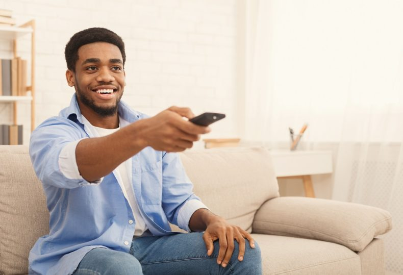 Watching TV at home. Young african american man having rest, switching channels with remote controller, empty space