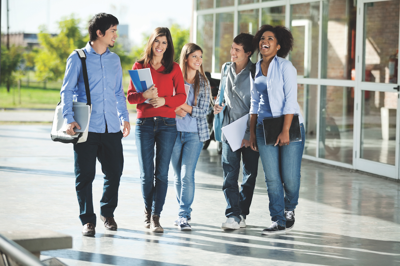 Full length of cheerful university students walking on campus