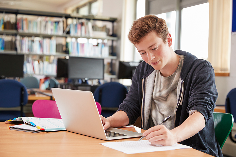 male-student-working-at-laptop-in-college-library-PBDVK7H