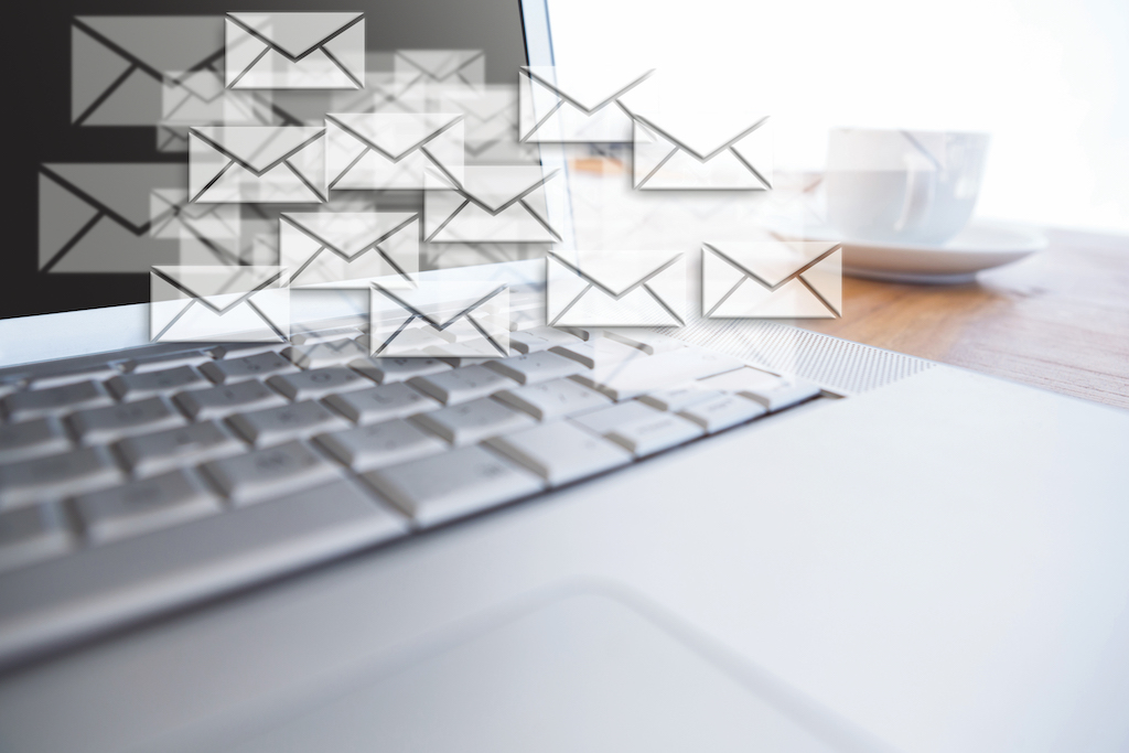 Digital composite of New mails appearing beside laptop